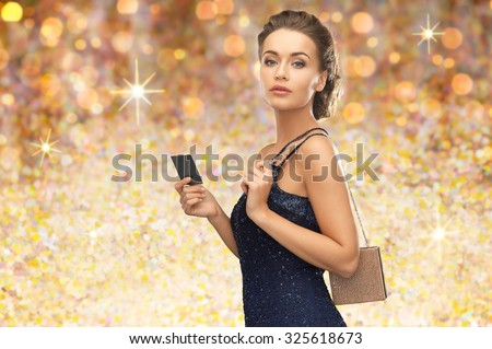people, luxury, holidays and finance concept - beautiful woman in evening dress with vip card and handbag over golden lights background - stock photo