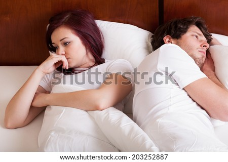 People lying together but separately because of marital problems - stock photo