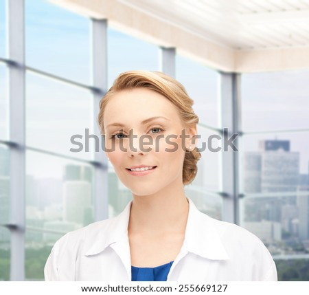 people, medicine and profession concept - smiling young female doctor over clinic background - stock photo