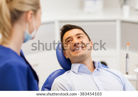 people, medicine, stomatology and health care concept - female dentist talking to happy male patient at dental clinic office - stock photo