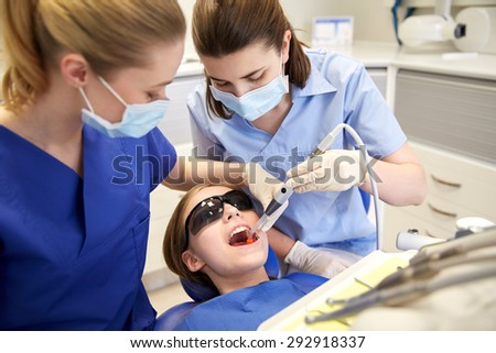 people, medicine, stomatology and health care concept - female dentists with mirror and suction treating patient girl teeth at dental clinic office - stock photo