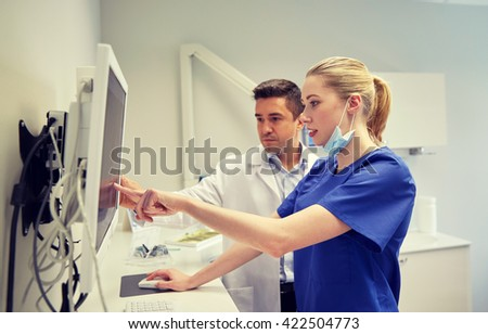 people, medicine, stomatology, technology and health care concept - dentists looking to x-ray scan on monitor at dental clinic - stock photo