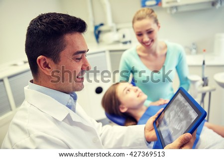 people, medicine, stomatology, technology and health care concept - happy male dentist looking at teeth x-ray on tablet pc computer and patient girl with her mother at dental clinic office - stock photo