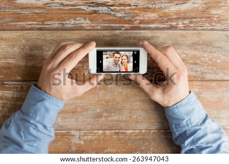 people, memory, relations and technology concept - close up of male hands holding smartphone with photo of happy couple on screen at table - stock photo