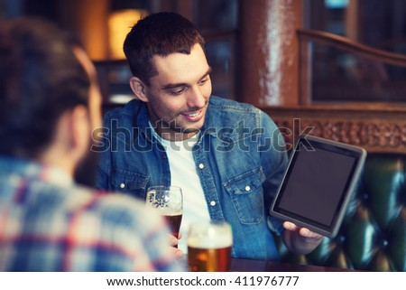 people, men, leisure, friendship and technology concept - happy male friends with tablet pc computer drinking beer at bar or pub - stock photo