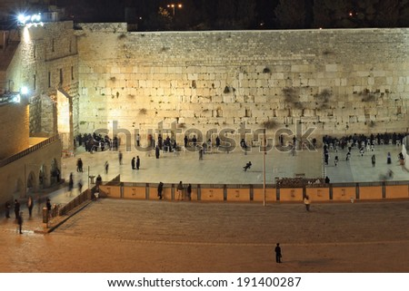 People, mostly soldiers praying at the holiest Jewish site - Western/Wailing wall at night - stock photo