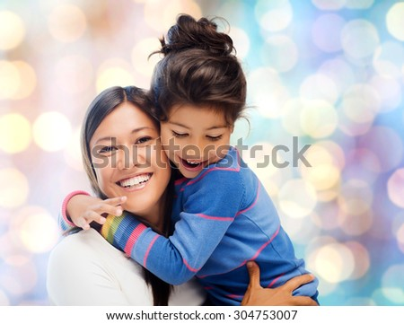 people, motherhood, family and adoption concept - happy mother and daughter hugging over blue holidays lights background - stock photo