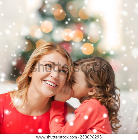 people, motherhood, family, christmas and adoption concept - happy mother and daughter whispering something into ear at home - stock photo