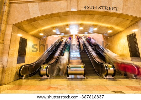People moving on a escalator. Fast moving blurred picture. - stock photo