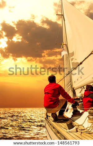 People on sailing boat in the sea at sunset  - stock photo