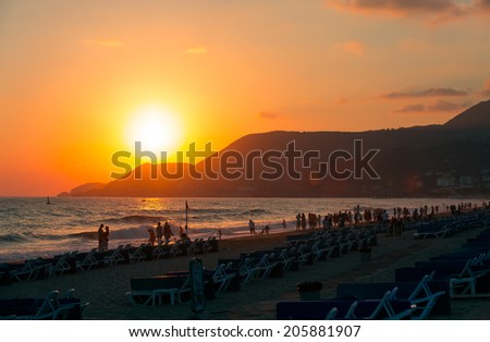 people on the beach during the sunset  - stock photo