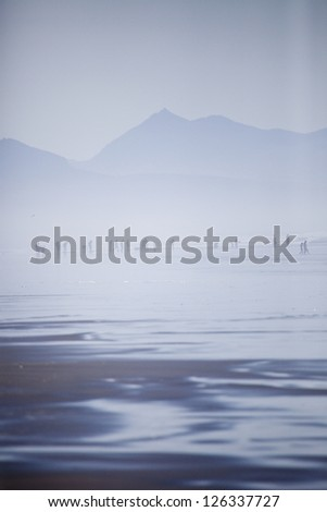 People on the beach in the fog: Fort Stevens State Park, Oregon Coast - stock photo