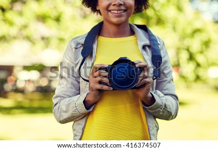 people, photography, technology, leisure and lifestyle - close up of happy young african american female photographer with digital camera in summer park - stock photo