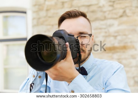 people, photography, technology, leisure and lifestyle - happy young hipster man holding digital camera with big lens taking picture on city street - stock photo