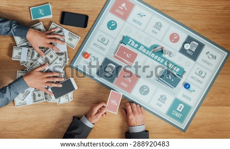 People playing a business board game on a wooden table, one player is holding a lot of money and winning, hands top view - stock photo