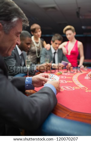 People playing at the poker table in casino - stock photo