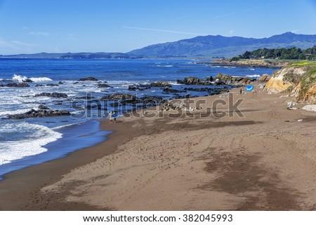 People playing on the beach & searching for sea shells, blue sky & aquamarine sea, waves crashing on the sand, at Moonstone Beach, along Big Sur Coast, California Central Coast, near Cambria CA. - stock photo