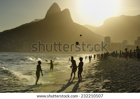 People playing soccer at sunset, Ipanema Beach, the world famous beach, in Rio de Janeiro, Brazil - stock photo