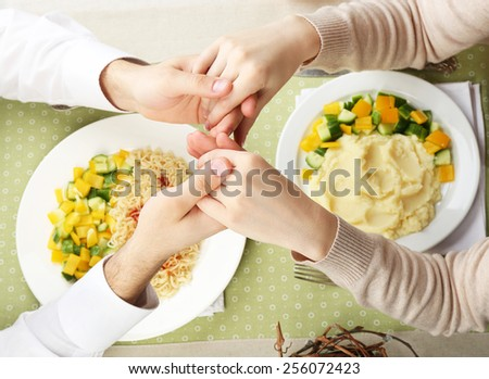 People praying before eating, top view - stock photo