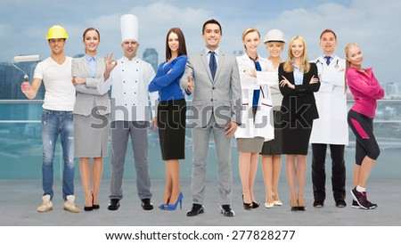 people, profession, qualification, employment and success concept - happy businessman with group of professional workers showing thumbs up over city background - stock photo