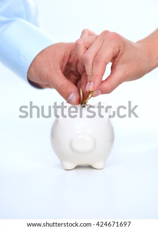 People putting coin into the piggy bank - stock photo
