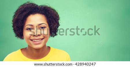 people, race, ethnicity and portrait concept - happy african american young woman face over green chalk board background - stock photo
