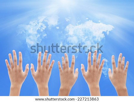 People raising hands on world map of clouds background. International Volunteer Day for Economic and Social Development, Human Rights Day, World Religion Day concept. - stock photo