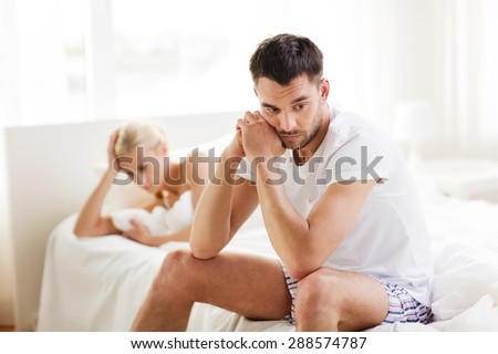 people, relationship difficulties, conflict and family concept - unhappy couple having problems at bedroom - stock photo