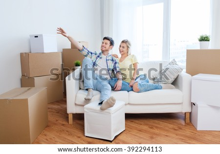people, repair and real estate concept - smiling couple with boxes moving to new home and dreaming - stock photo