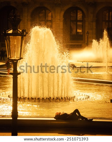 People rest near Louvre museum fountains. Selective focus on the water splashes. Aged photo. Vignette. - stock photo