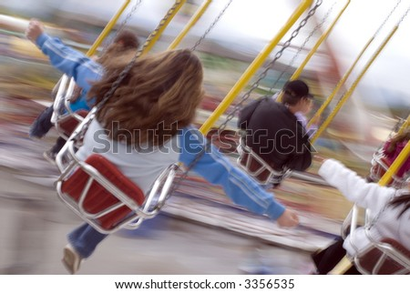 People riding fairground swings. (Shot with full motion blur.) - stock photo