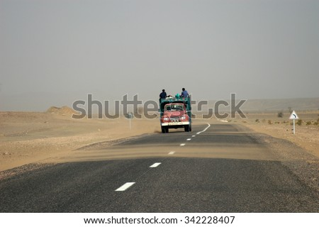 People riding on the roof of an old truck on a sandy road - stock photo