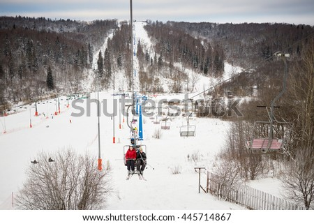 People rise on cableway on winter day at ski resort. - stock photo