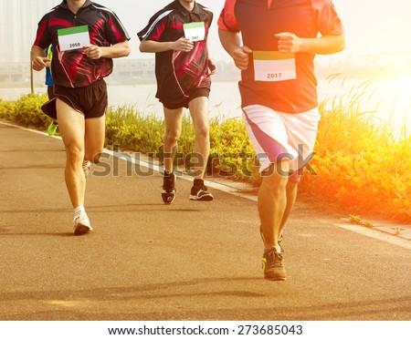 People running fast in a city marathon on street - stock photo
