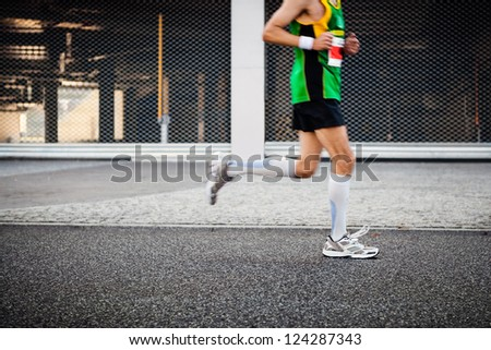 People running in marathon on city street, motion blur. Exercising and sport outdoors. Selective focus on sport shoe. - stock photo