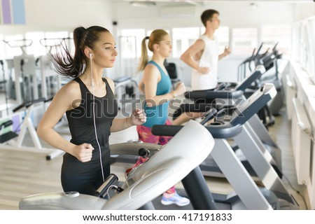 People running on treadmill at gym - stock photo