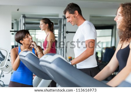 People Running on Treadmill in the Gym - stock photo