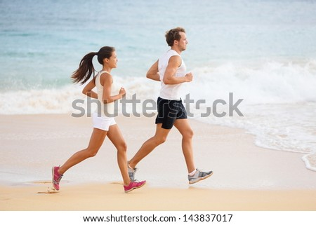 People running - runner couple on beach run jogging outdoors. Fit man athlete and woman fitness runners working out together running on beautiful beach. Multi-ethnic couple. - stock photo