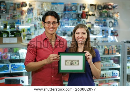 People running small family business, with asian shop owner and caucasian wife in computer store, showing their first dollar to the camera and smiling - stock photo