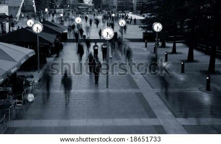 People rushing around clocks - stock photo