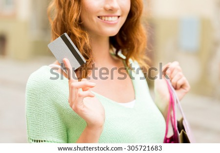 people, sale and consumerism concept - close up of happy woman with shopping bags and credit card on city street - stock photo