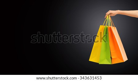 people, sale, consumerism, advertisement and black friday concept - close up of hand holding shopping bags - stock photo