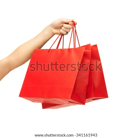 people, sale, consumerism, advertisement and commerce concept - close up of hand holding red blank shopping bags - stock photo