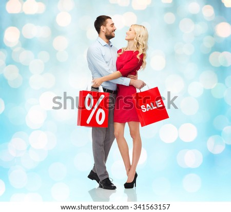 people, sale, discount and christmas concept - happy couple with red shopping bags hugging over blue holidays lights background - stock photo