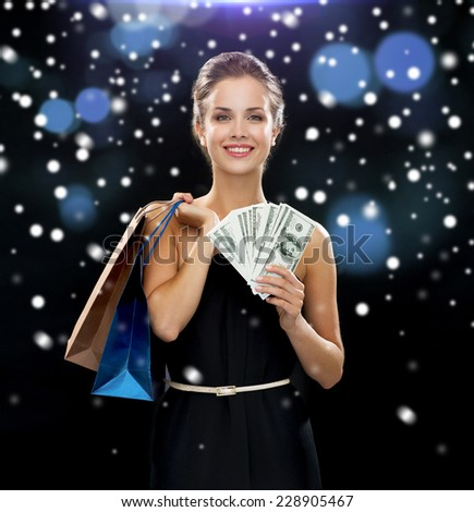 people, sale, gifts, money and holidays concept - smiling woman in dress with shopping bags and money over snow and night lights background - stock photo