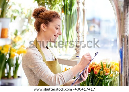 people, sale, retail, business and floristry concept - happy smiling florist woman with clipboard writing and making notes order at flower shop - stock photo