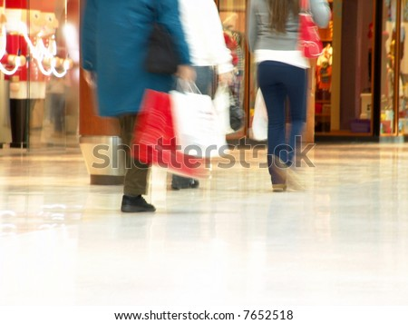 People shopping inside a mall (Focus is more on the front areas & sharpness is a little off to highlight motion & obscure logos/faces, photo composition allows you to add text & other contents easily) - stock photo