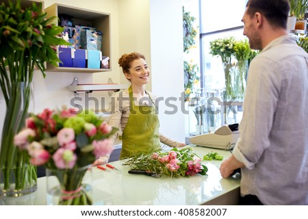 people, shopping, sale, floristry and consumerism concept - happy smiling florist woman and man or customer talking at flower shop - stock photo