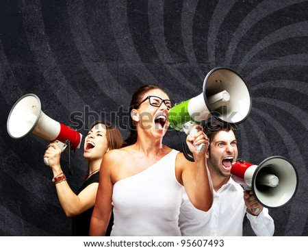 people shouting with megaphone against a grunge wall - stock photo