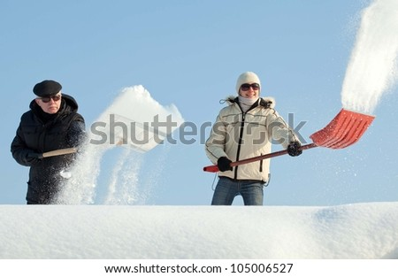 People shovelling snow on a roof against blue sky - stock photo